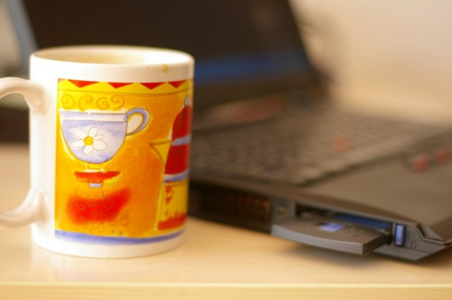 A cup of coffee and a ThinkPad on the table
