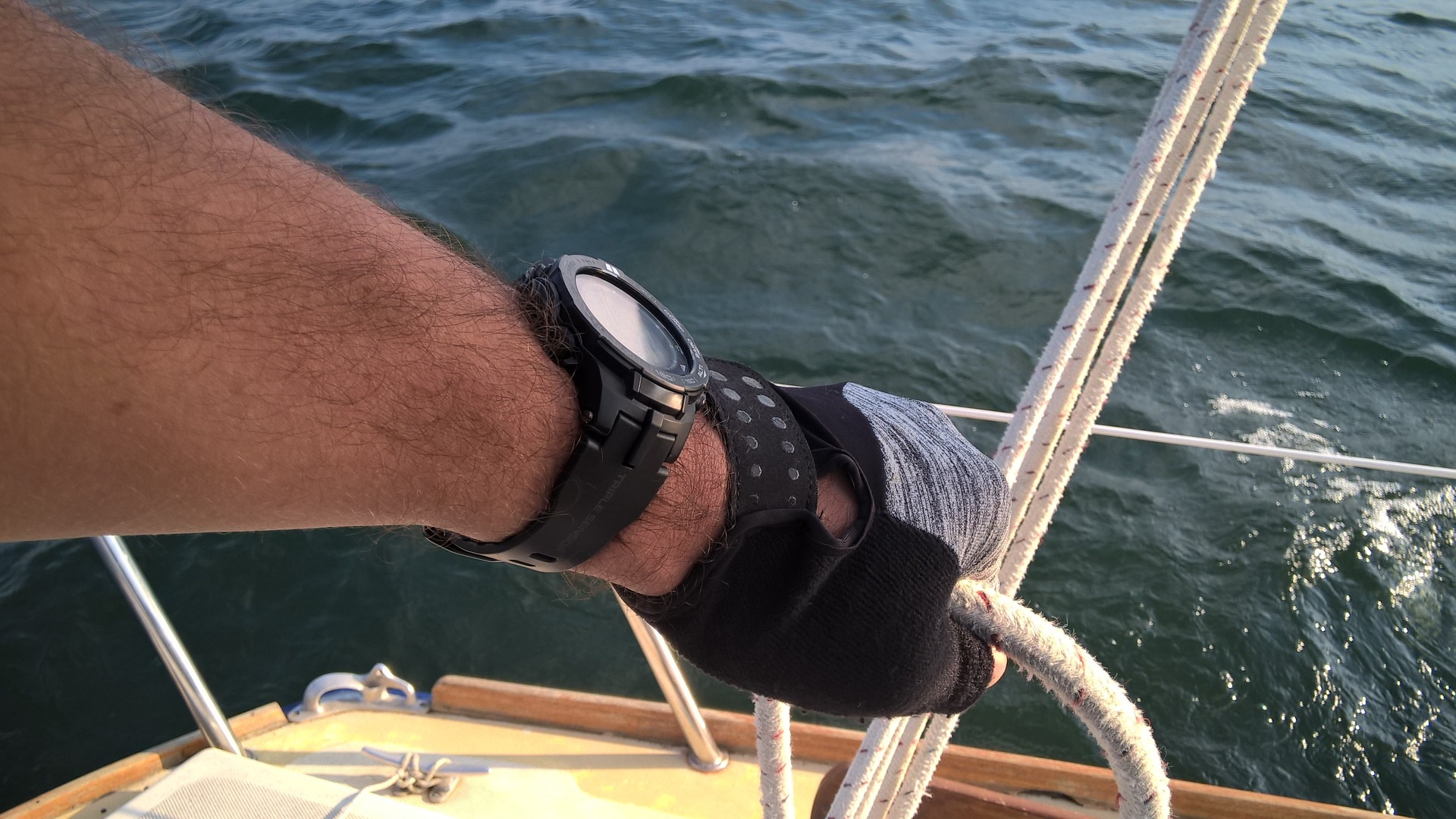 Photo of me sailing in stronger winds (detail -- holding the mainsheet)